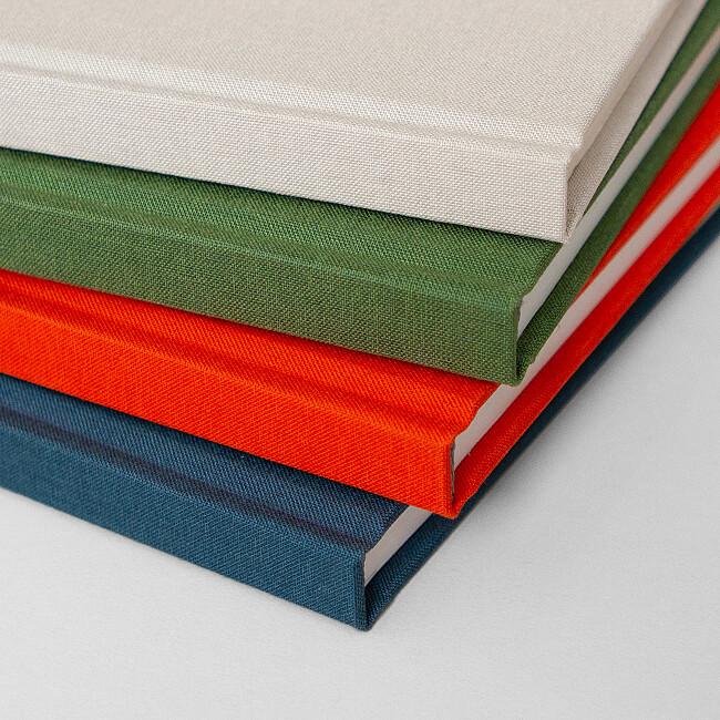 Dos des carnets rouge, vert, beige et bleu